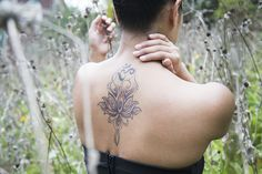 Deborah Thach's fourth tattoo depicts a lotus flower blooming into an Om sign on her upper back. Her other tattoos include the words