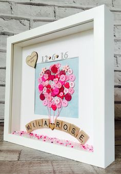 New Baby Frame A perfect keepsake for a loved one to treasure and ideal as a gift to celebrate the birth of a baby boy or girl. The frame measures approximately 23cm by 23cm and available in white. Included in the frame is the babys name made from wooden scrabble letters and a balloon made completely from different size buttons of your choice, these are typically pink, blue or can be cream if the sex is still unknown. The birth date can be added at the bottom either using glitter letters…