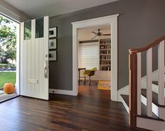 Dark stained hardwood floors make for a warm welcoming entryway into this craftsman style home. The front door gets a modern update with glass panels set high on the door. Gray walls make a nice contrast with the white molding over the doorway to the next room.