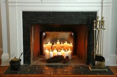 Non working fireplace decorating idea ~ just be careful to monitor the amount of heat the candles are putting out if you have blocked the chimney with insulation of any type. Change out the cones for mock greenery, mock autumn leaves, some silk flowers or other seasonal items as fitting just scattered in front.