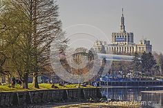 Bucharest, Romania - March 09, 2013: People relax on the bank of the lake in Herastrau park. House of the Free Press in the background, the tallest edifice in the city between 1956 and 2007.