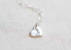 Cute https://www.etsy.com/listing/73683948/tiny-hammered-heart-necklace-sterling