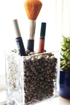 Spray painted coffee beans and an old candle votive make the perfect make-up holder