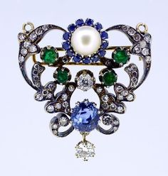"""A convertible necklace pendant / brooch in 14 or 15 karat yellow gold, comprising a sky blue nearly round oval sapphire centerpiece, as well as garnished with diamonds, Colombian emeralds and a round white pearl atop. Gross weight of the piece is 17.8 grams and measures 40mm (1.58"""") tall and 37mm (1.46"""") wide. The reverse of the necklace pendant has an additional safety pin in case it is worn as a brooch."""