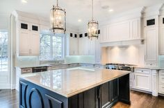 A pair of glass and nickel lanterns hang over a black kitchen island accented with decorative trim moldings topped with Taj Mahal Quartzite.