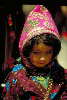 Yemen, Girl wearing a bonnet called a Qarqush - Qarqush is a kind of head covering that made out of colored fabric—usually cotton or satin—and decorated with silver, coral and shells. The garment has ancient, perhaps pre-Islamic roots.
