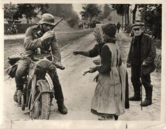 """1939- German civilians offer their liberator a drink as German troops advanced """"somewhere"""" in Poland."""