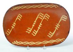 """Garth's Sale 1114 Lot 655. May 17 2014. REDWARE LOAF PAN.  American, mid 19th century. Coggled rim and linear yellow slip decoration. Flakes and hairline. 11.5"""" x 17"""".  Estimate $ 800-1,600."""