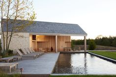 Massachusetts architect Maryann Thompson designed this pool house overlooking a grassy expanse as an addition to a coastal Martha's Vineyard house she also renovated, whose mostly white interiors are by Shelter. Photo by Emily Johnston Bauhaus, Hampton Pool, Outdoor Spaces, Outdoor Living, Shelter Design, Barn Siding, Modern Pools, Modern Pool House, Modern Gazebo