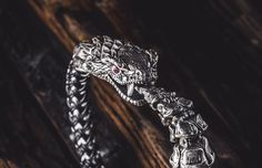 Snake bracelet in sterling silver with inlaid red Topaz gemstone, braided rubber and stainless steel.