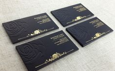 An elegant black business card with embossed detailing and gold foil stamping