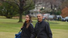 US President Barack Obama and daughter Malia make their way across the South Lawn upon return to the White House in Washington, DC on January 4, 2015