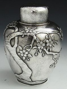 Antique Japanese sterling silver antique tea caddy with pull off cap and interior push in cap, circa 1900.  The surface has very fine hammering with an embossed tree with blossoms.