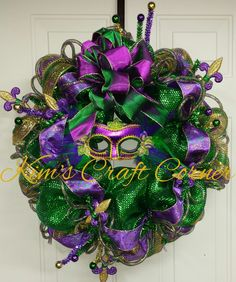 Decorate for Mardi Gras! Kim's Craft Corner's Mardi Gras Wreath. It is made of purple and green ribbons and mesh and featured a mask in the center. #scottsmarketplace