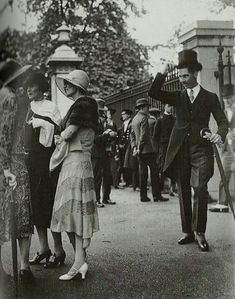 а gentleman tips his hat to a group of ladies in the 1920s.