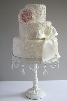Pretty white lace wedding cake with pale pink peony fondant and ivory satin ribbon bow. Chandelier cake stand by FOXYQUEEN