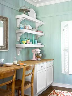 Opposite the sink wall, a butcher-block countertop offers uninterrupted work space. When needed, the spot also works for casual dining. Shapely shelving keeps colorful dishes and serving pieces within easy reach. Bulky items stow easily in base cabinets.