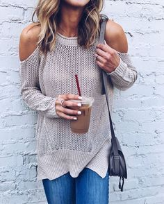 Tanned caramelette in knit taupe cold-shoulder untucked sweater, blue fitted denims w/ graphite shoulderbaG