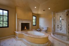 A spacious bathroom with a center tub. Behind the soaking tub is an open-hearth fireplace. Would you feel comfortable with a fireplace in your bathroom? Source: http://www.zillow.com/digs/Home-Stratosphere-boards/Luxury-Bathrooms/