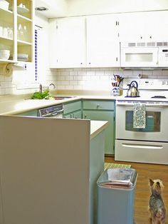 My dream kitchen!  A little retro and very affordable!  They painted cabinets (the lower cabinets are TIDEWATER by Martha Stewart) and added subway tile (my fav.) with grout to match the existing laminate countertops.