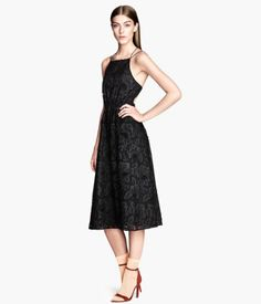 Calf-length, backless lace dress with narrow shoulder straps. Elasticized waist and flared skirt. Lined.