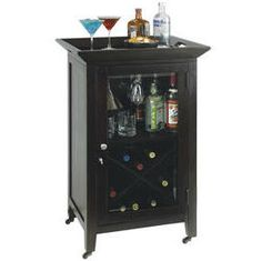695074 Howard Miller wine console | BUTLER The Butler Bar features a compact and simple design. Made of select hardwoods and veneers with a Black Coffee finish with brushed satin nickel hardware. Has a removable top serving tray for entertaining guests! The beveled glass door locks for security. Inside the cabinet is a wood stemware rack, storage for spirits and accessories, and a 14 bottle wine rack, four antique brass ball casters.