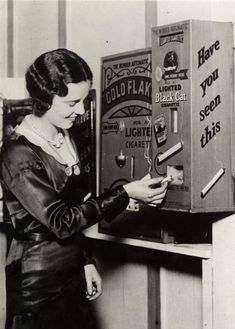 A vending machine that sold already lit cigarettes for a penny. England, 1931.