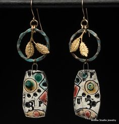 The Assassination of Painting earrings, rustic clay dangles in multiple colors, like a Miro, hang below verdigris hoops with golden leaves