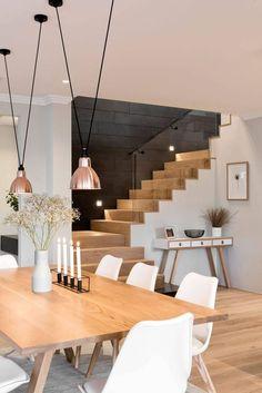 Salon avec escalier, mur noir avec plaques d'ardoise. Chic, moderne et chaleureux grâce au blanc et au bois / Devis gratuit sur www.gares-conception.com