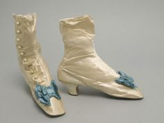 Woman's Buttoned Boots  Made in Philadelphia, Pennsylvania, United States, North and Central America  Late 1860-70s  Henry Wireman, American, Philadelphia  Off-white silk satin, blue silk ribbon, leather8 x 21/2 x 81/2 inches (20.3 x 6.4 x 21.6cm) Heel Height: 2 inches (5.1cm)  Currently not on view  1996-19-28a,b  Gift of the heirs of Charlotte Hope Binney Tyler Montgomery, 1996