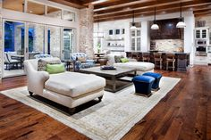 Modern Living Room Design with stone walls beam ceiling wide plank wood floors and velvet turquoise accent stools
