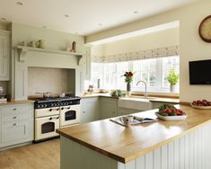 photo of bespoke farmhouse farmhouse kitchen shaker traditional warm sage sage green harvey jones kitchen with belfast sink white walls and ...