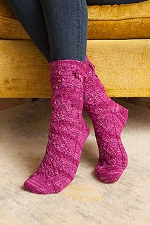 """These wonderful toe up socks are as fun to knit as they are to wear! The detailed cables or """"leaves & vines"""" wind up the foot, with buds at the ankle and then roses that bloom (bobble clusters) at the top."""