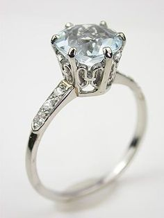Antique Aquamarine Engagement Ring, RG-1408, An aquamarine  is set in a platinum coronet shank. Six old style full cut diamonds cascade down the shoulders of the platinum band, lending the illusion of drizzling dew drops to this antique engagement ring. Details: Platinum. Old style full cut diamonds; 0.19 carats. Round aquamarine; 2.06 carats. Antique, Circa 1925. Ring Size 8.0