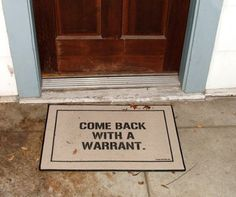 """The """"Come Back With A Warrant"""" doormat is a funny quip aimed at unwanted guests knocking on your door."""