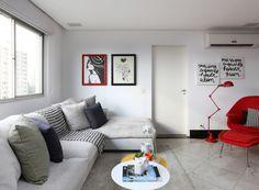 No estar, a arquiteta Duda Senna empregou um sofá (Dpot) bem confortável, com formato L (à esq.). A tonalidade clara do estofamento conversa com o tapete cinzento (Sol & Art), também aconchegante. Diante das cores neutras, o vermelho vibrante da poltrona Womb, de Eero Saarinen (à dir.), se destaca