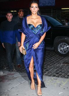 Kim Kardashian was stealing the limelight on her sisters party. The 33-year-old looked jaw-dropping in a dress that featured a green and blue corset, enhancing her already impressive cleavage. The rest of the dress was blue satin with green detailing and featured a sexy split up the front, cinching in at her waist and leaving her legs on show. Kim also sported a pair of gold chain T-strap sandals and wore her raven locks in a ponytail, with heavy make-up completing her look.