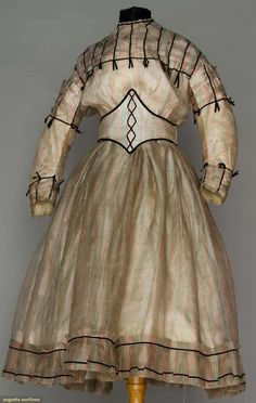 "1865 Girl's Dress - 2 bodices. Transparent silk gauze w/ red, black & white stripes, 3-piece dress, blouse, button-on skirt & Swiss waist, all trimmed in very narrow black velvet ribbon, W 20"", L 37"", (grey tinge) very good; t/w 1 woman's blouse of same silk fabric. Brooklyn Museum. August Auctions 2011"