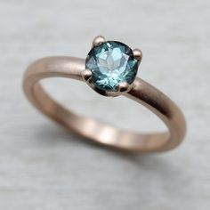 Our eco-friendly & conflict-free 5mm Crown Solitaire Engagement Ring, in matte recycled 10k rose gold with a fair trade aqua blue Malawi sapphire.