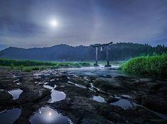 KAGAYA @KAGAYA_11949  5月20日 その月は、悠久の自然がつくった大地の上、 銀色の月光をなげ、かすかな光の輪をまとっていました。 (大分県、原尻の滝上流にて一昨日未明撮影)