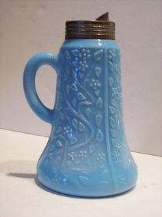 "Blue milk glass syrup pitcher. Challinor-Taylor's ""Tree of Life"" pattern."