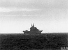 The aircraft carrier HMS Invincible silhouetted against the horizon as she sails towards the Falkland Islands. 1982.