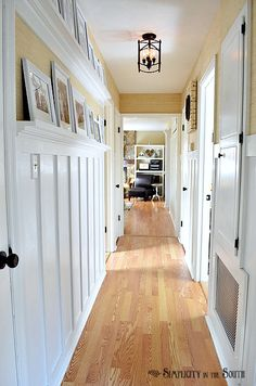 Board and batten hallway with gallery shelves. Our hallway isn't this long, but it is this narrow and it would be lovely to display photos here!