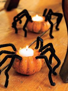 Scooped-out mini pumpkins become spidery votives, thanks to tealights and pipe cleaners. #halloween