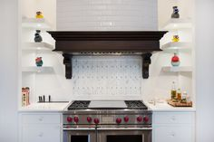 A custom mantle shelf and tile hood set off the range alcove, surrounded with colorful vases to line the space on lit corner shelving. A beautiful kitchen design.