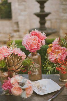 gold painted bottles, photo by Day 7 Photography http://ruffledblog.com/metallic-garden-wedding-inspiration #centerpieces #reception #pink