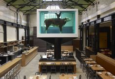Tramshed restaurant. Dining beneath a suspended formaldehyde-preserved cow - an installation by Damian Hirst - and a menu designed around chicken and steak to share, alongside seasonal starters and puddings. That's exactly what this outpost from restaurateur Mark Hix is about. Tramshed, 32 Rivington St, London EC2A 3EQ, chickenandsteak.co.uk