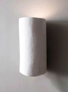 Curved and sculpted in plaster, the Serenity wall light by Hannah Woodhouse is the perfect wall sconce for spas, hotels and residential interiors.