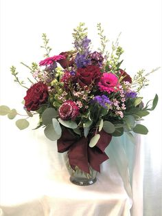 Roses, gerbera daisy, larkspar, statice, waxflower