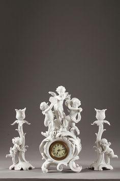 Une garniture de cheminée en biscuit sur le thème des amours musiciens, composée d'une pendulette et d'une paire de bougeoirs. Le cadran à chiffres romains pour les heures...